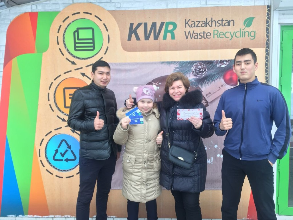 Aibek Rakhim (L) with residents who got tickets for the return of recyclables.