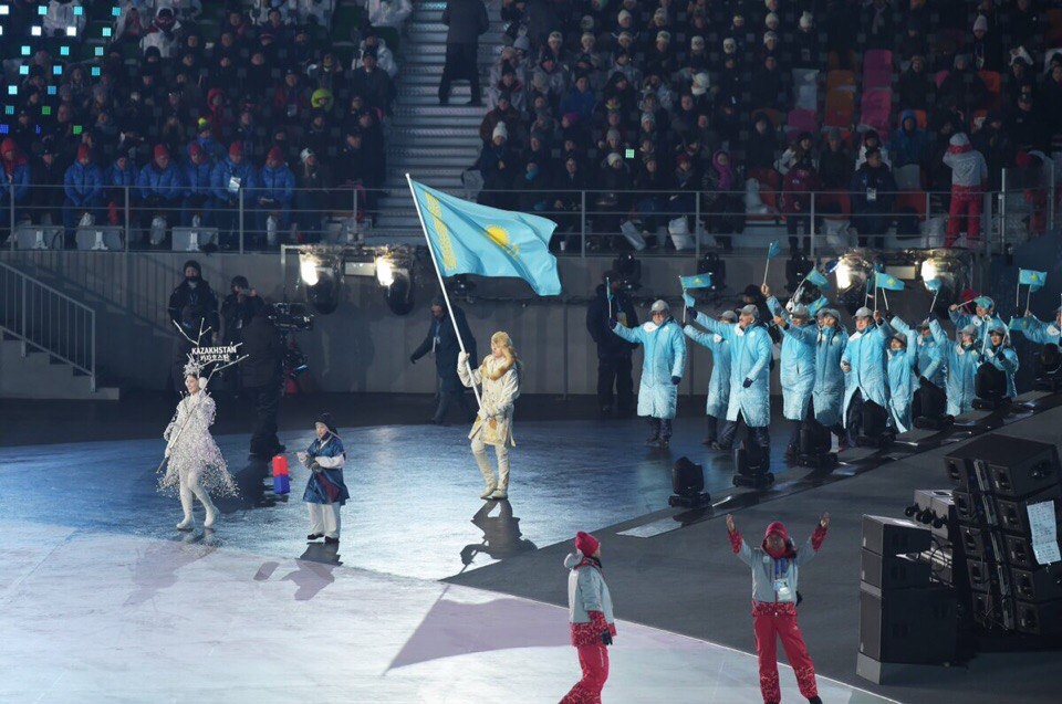 Abzal Azhgaliyev carrying the flag. Photo credit: National Olympic Committee press service